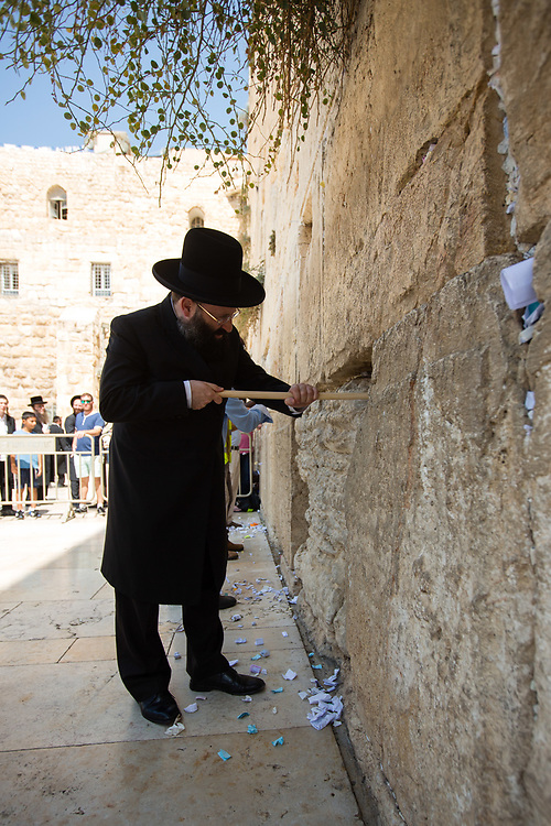Western Wall Rabbi Shmuel Rabinowitz removes notes containing prayers and messages which were left by visitors, from the cracks between the stones of the Western Wall, Judaism's holiest prayer site, in the Old City of Jerusalem, Israel, on September 17, 2017. The clean-up which takes place ahead of the upcoming Jewish New Year Holiday, clears the wall's crevices and frees up space for more notes that people of all faiths slip between its stones, believing that requests deposited at the site are more likely to be heard by God.