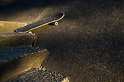 A skateboard lies wedged between a concrete ramp and a flight of stairs outside Medgar Evers Pool near Garfield High School in Seattle, Washington.