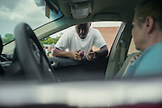 """BIRMINGHAM, AL – SEPTEMBER 10, 2015: Quintarius Monroe (center) checks his blood sugar outside Sonya Whitaker's car before the start of football practice at Woodlawn High School. A type 1 diabetic, Monroe requires frequent blood sugar testing and supervision when self-administering insulin. When care from qualified personnel at his school in Center Point became unavailable, Monroe was forced to transfer several miles away from his locally zoned school to attend Woodlawn High School. The Americans with Disabilities Act requires schools to provide """"reasonable accommodation"""" for students with medical conditions, but given that most schools no longer retain school nurses, many schools are failing to provide adequate care for their students.<br /> CREDIT: Bob Miller for The New York Times"""