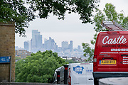With the skyscrapers of the City of London, the capital's financial district, in the distance, motorists in morning rush-hour traffic, turn down Sydenham Hill, on 15th June 2021, in south London, England.
