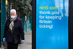 © Licensed to London News Pictures. 31/03/2020. London, UK. A man wearing a face mask walks past 'NHS Staff, thank you for keeping Britain ticking!' coronavirus public information poster in north London as lockdown continues. Photo credit: Dinendra Haria/LNP