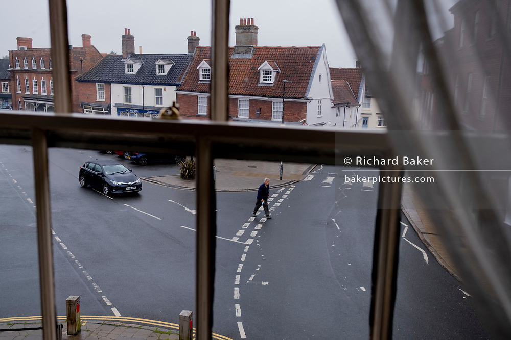 An evening viewpoint through a sash window of a pedestrian walking through a  road junction and a market place of closed shop businesses in a rural Norfolk town, on 30th June 2021, in Aylsham, Norfolk, England.