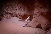 Nude woman sitting against a wall in Leprechaun Canyon, Hanksville, Utah