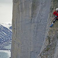 Stewart Valley, Baffin Island, Nunavut, Canada. A mountaineer free climbs high on Great Sail Peak's huge north face.