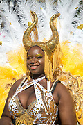 Hackney Carnival on 8th September 2019 in London, United Kingdom. Smiling dancer with gold horns and feathered headdress.