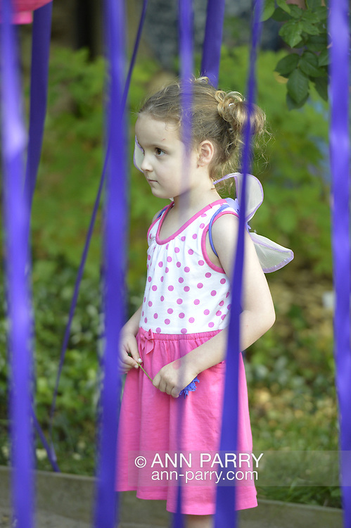 Old Westbury, New York, U.S. - June 21, 2014 - CRISTINA KIRCHHOFER, 4 1/2 years old, of Bayside, is one of many young girls who wore fairy wings to see the Lori Belilove & The Isadora Duncan Dance Company dance throughout the gardens during the Midsummer Night event at the Long Island Gold Coast estate of Old Westbury Gardens on the first day of summer, the summer solstice. Cristina is surrounded by long purple ribbons hanging from a trellis roof.