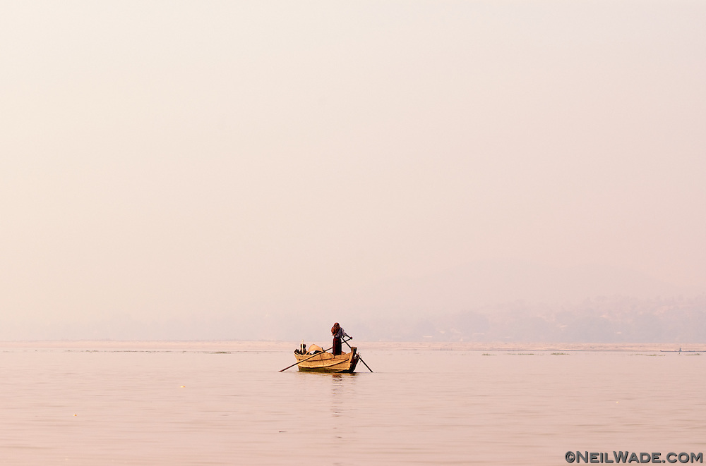 A lone boat sails down the Ayeyarwady (Irrawaddy) river near Mandalay, Myanmar (Burma).  The white haze in the air is actually smoke from the rampant use of slash and burn farming in the area.