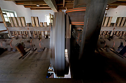 The De Ster Snuff and Spice mill in Rotterdam, The Netherlands.<br /> The camshaft which is 40 cm in diameter and 11 meters long, drives the edge mill and powers the giant blades in the chopping room below. The Wallower on the main shaft, (the small horizontal wheel with orange bands) drives the camshaft when the wheel is engaged and connected to the large vertically mounted camshaft wheel. (Photo © Jock Fistick)