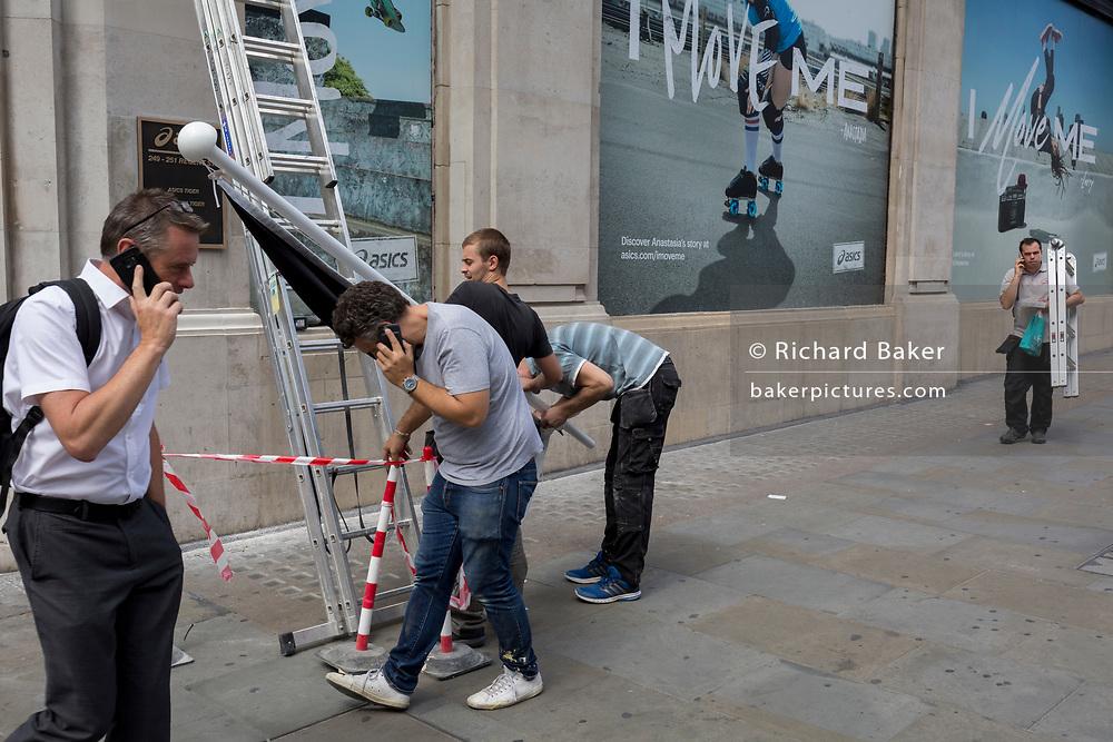 Pedestrians pass workmen preparing to erect a shop flag for sportswear retailer Asics, on 1st August 2017, in Regent Street, London, England.