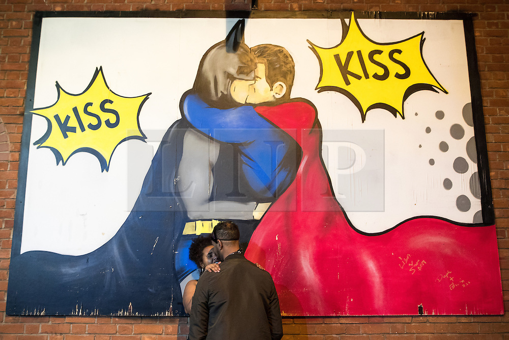 """© Licensed to London News Pictures . 30/10/2016 . Manchester , UK . A couple kiss beneath a pop art mural of Batman and Superman kissing , off Canal Street in the """" Gay Village """" . Revellers on a night out , many in fancy dress , on the weekend before Halloween . Photo credit : Joel Goodman/LNP"""