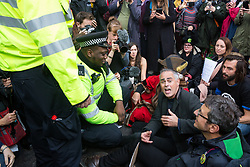 London, UK. 16 October, 2019. A Metropolitan Police officer prepares to arrest Jonathan Bartley (c), co-leader of the Green Party, Guardian journalist George Monbiot (r) and a group of climate activists from Extinction Rebellion using Section 14 of the Public Order Act 1986 after they sat in the road in Whitehall following a People's Assembly in Trafalgar Square as part of a protest against the use by the Metropolitan Police of Section 14 so as to prohibit entirely Extinction Rebellion Autumn Uprising protests throughout the capital.