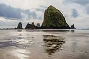 Pounding surf eroded bluffs away, leaving Haystack Rock, a 235-foot high sea stack rising from the Pacific Ocean, at Cannon Beach, Tolovana Beach State Recreation Site, Oregon coast, USA.