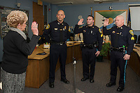 Ann Kaligian with Chief Chris Adams swears in Detective Benjamin Black and Detective Kevin Butler during the Laconia Police Commissioners meeting at City Hall Thursday afternoon.  (Karen Bobotas/for the Laconia Daily Sun)