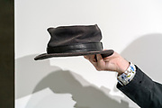 fashionable hat being hold up against a white background