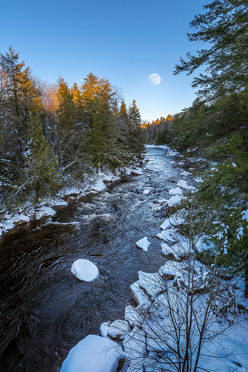 A near full moon appears above the Blackwater River enveloped in a coating of snow on a crisp January evening.