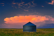 pink clouds at sunset with grain bin and storm sky<br /> Bengough<br /> Saskatchewan<br /> Canada