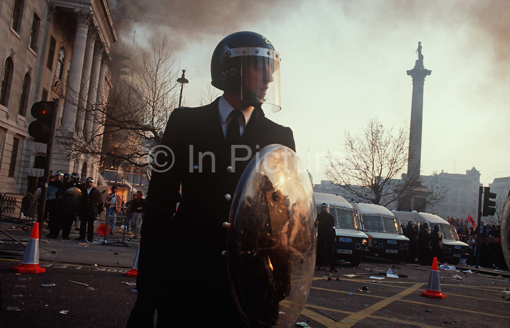 Riot police officers stand firm in Trafalgar Square at the height of the Poll Tax Riot on 31st March 1990, in Westminster, London, England. Angry crowds, demonstrating against Margaret Thatchers local authority tax, stormed the Whitehall area and then Londons West End, starting fires and overturning cars, looting stores up Charing Cross Road and St Martins Lane. The anti-poll tax rally in central London erupted into the worst riots seen in the city for a century. Forty-five police officers were among the 113 people injured as well as 20 police horses. 340 people were arrested.