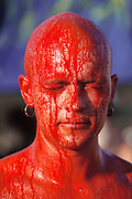 A man with a shaved head gets painted red at Burning Man. Burning Man is a performance art festival known for art, drugs and sex. It takes place annually in the Black Rock Desert near Gerlach, Nevada, USA.