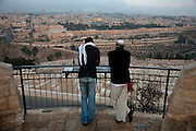 Two visitors standing at the  Mount of Olives, Israel, look out over the cemetery toward the gold-leafed Dome of the Rock, the most famous Islamic monument in the Old City of Jerusalem. (From the book What I Eat: Around the World in 80 Diets.)