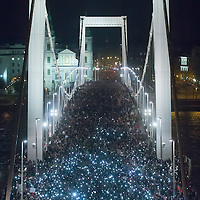 Participants hold their phones in the air to protest against the planned Internet tax as they march through a bridge in Budapest, Hungary on October 28, 2014. ATTILA VOLGYI