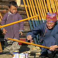MONGOLIA, Darhad Valley.  Herding family paints roof supports for their ger (yurt).