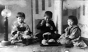 Three Japanese children seated on cushions on the floor,  eating noodles with chopsticks. Early 20th century.