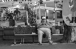 obese man with a cellphone sitting on a bench at a fair in New Mexico
