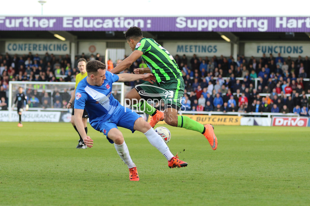 Lyle Taylor forward for AFC Wimbledon (33) and Hartlepool United defender Carl Magnay (2) tussle the ball during the Sky Bet League 2 match between Hartlepool United and AFC Wimbledon at Victoria Park, Hartlepool, England on 25 March 2016. Photo by Stuart Butcher.