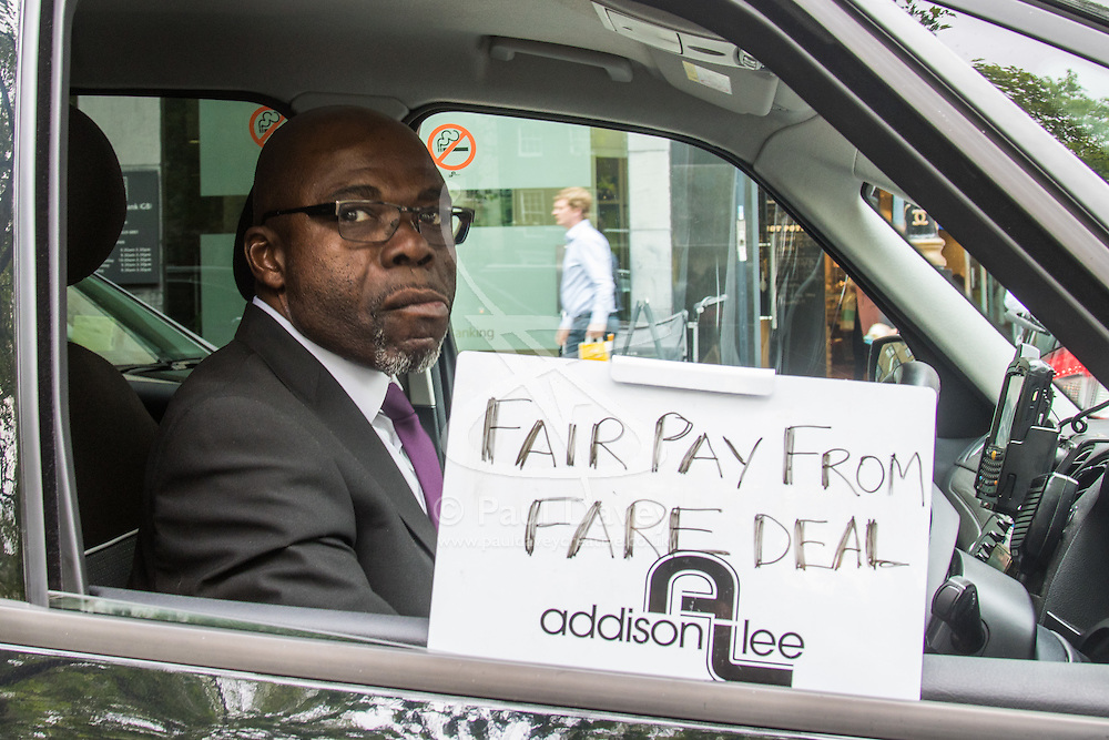 """Mayfair, London, May 24th 2016. Drivers from minicab operator Addison Lee bring traffic to a standstill in Berkely Square, outside of the offices of owner Carlyle Group, in protest against new """"unfair"""" pay rates as the company battles to compete with cut-price Uber, with some drivers claiming they are earning as little as £4.99 per hour. PICTURED: A driver demands fair pay from the fares that he earns Addison Lee."""