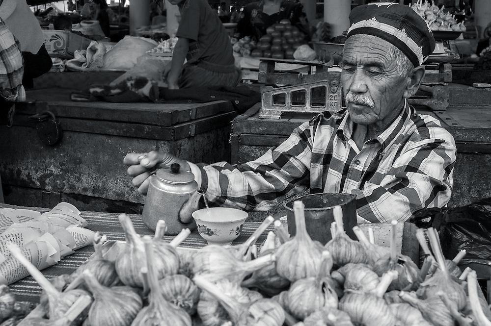 Portrait of an old Tajik man pouring a cup of tea behind a pile of garlic bulbs in a market in western Tajikistan