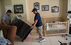 Oct 8, 2016 - Palo Alto, California, U.S. - Art Sandoval, right, moves a dresser with help from his brother-in-law, John Pineda, as they relocate to be near the hospital for the twins' upcoming separation surgery. (Credit Image: © Lezlie Sterling/Sacramento Bee via ZUMA Wire)