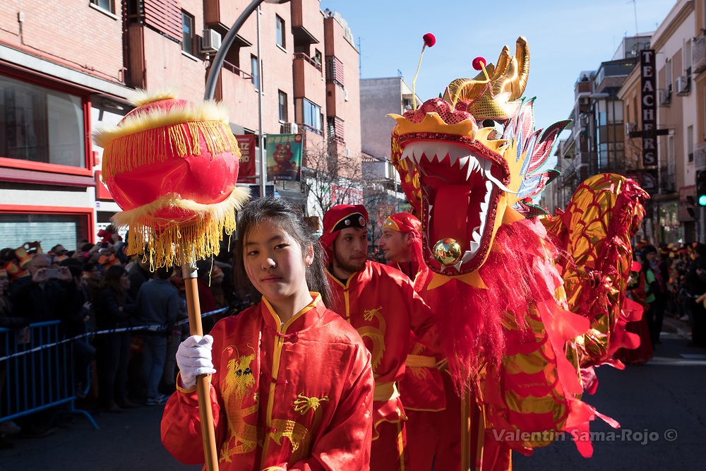 Madrid, Spain. 18th February, 2018. A girl leading a dragon using a red ball during the Chinese New Year parade in Madrid. © Valentin Sama-Rojo
