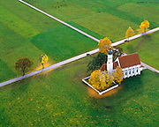 Autumn foliage lines the crossroads next to Bavaria's Saint Coloman's Church, as seen from an aerial perspective.