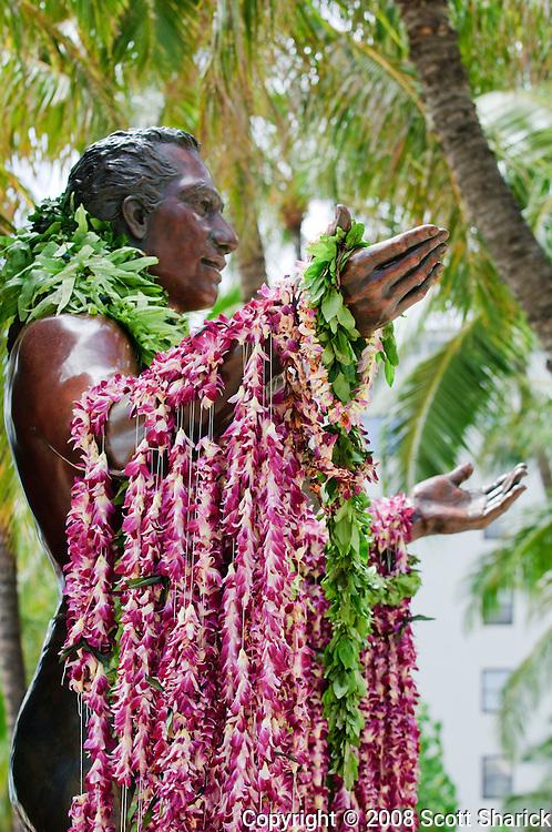 The Duke Kahanamoku statue in Waikiki, Hawaii draped with colorful lei.