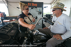 """Harley-Davidson's Chelsey Funke is helping Harley rider Dave Przygocki with finding the right handlebars using the """"Fit Shop"""" setup at Black Hills Harley-Davidson during the annual Sturgis Black Hills Motorcycle Rally. SD, USA. August 5, 2014.  Photography ©2014 Michael Lichter."""