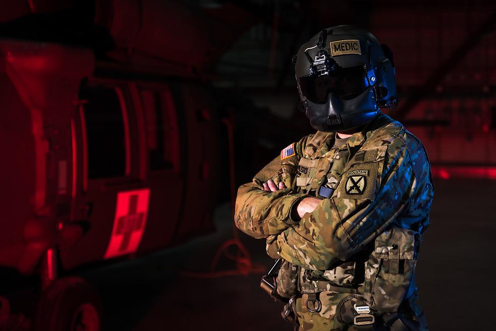 A U.S. Army Flight Paramedic (68WF2) stands next to a HH-60M Blackhawk in his Flight Helmet.