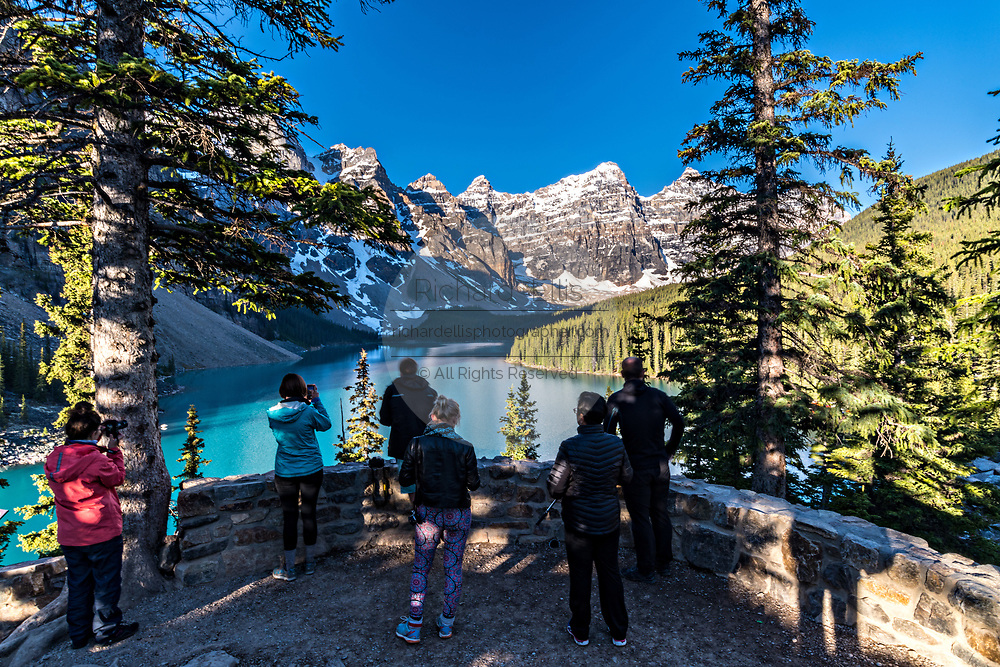 People view the scenic panorama of blue sky over the turquoise waters of Lake Louise and the snow dusted Fairview Mountain from the overlook in Banff National Park in Alberta, Canada.