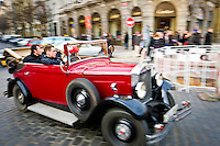 PRAGUE, CZECH REPUBLIC - MARCH 12th: Antique car with tourists touring the streets of Prague on March 12, 2011. Use of panning and motion blur.