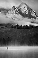 A kayaker paddles through the mist on Little Redfish Lake below the Sawtooth Mountains in Stanley, Idaho.