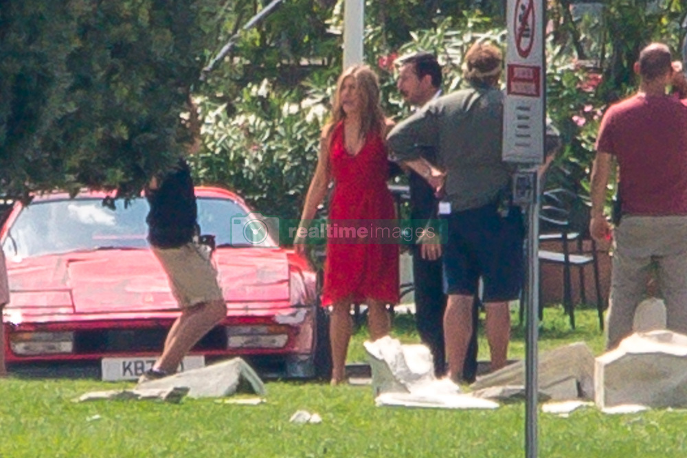 """EXCLUSIVE: Jennifer Aniston and Adam Sandler are currently filming """"Muerder Mystery"""" in lake Como. Today the location was Como town. The two actors were seen arriving on set with a caddy and then fiming a very agitated scene. With a car of carabinieri (italian police) crushed on a fake monument and Sandler surrendered after a car chase for which stuntman have been used. 10 Aug 2018 Pictured: Jennifer Aniston, Adam Sandler. Photo credit: MEGA TheMegaAgency.com +1 888 505 6342"""
