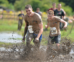 "© Licensed to London News Pictures. 28/07/2013. Competitors take part in the 2013 Tough Guy ""Nettle Warrior"" in Perton, Wolverhampton. Nettle Warrio is the Summer version of Winter Tough Guy. Run at the end of July it focuses less of the cold and more of the pain for the competitors. Photo credit:  Mike King/LNP"