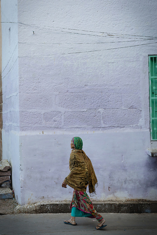 Woman in colourful sari walking past blue house in Jodhpur