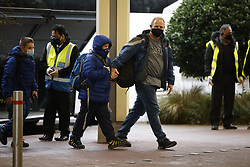 © Licensed to London News Pictures. 16/02/2021. London, UK. Passengers are surrounded by security guards as they arrive for quarantine at a Holiday Inn hotel near Heathrow Airport for the second day. People entering the UK from a 'red list' of 33 high risk countries will have to quarantine at hotels for 10 days to try and stop new coronavirus variants entering the country. Photo credit: Peter Macdiarmid/LNP