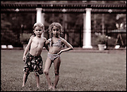 Two young friends stand for a photo while playing in the yard on summer break.