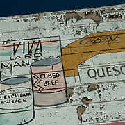 Painted signage reading Queso,Beans and related Hispanic foods on the side of peeled paint, concrete block building in San Diego.Building no longer exists.