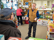 "25 FEBRUARY 2020 - BUTTERFIELD, MINNESOTA: MARK WARNER (center) owner of the True Value Hardware Store in Butterfield, MN, talks to a shopper in the grocery section. Butterfield is a farming community of about 500 people 130 miles southwest of the Twin Cities. The town has been a ""food desert"" for 10 years after its only grocery store closed in 2010. Barb Mathistad Warner and Mark Warner purchased the True Value store in Butterfield in December, 2018 and started selling groceries in the store in May, 2019. For residents of Butterfield going to a grocery store meant driving 10 miles to St. James, MN, or 20 miles to Windom, MN, the two nearest communities with grocery stores. The USDA defines rural food deserts as having at least 500 people in a census tract living 10 miles from a large grocery store or supermarket. There is a convenience store in Butterfield, but it sells mostly heavily processed, unhealthy snack foods that are high in fat, sugar, and salt.   PHOTO BY JACK KURTZ"