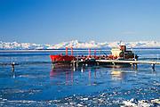 Alaska. Cook Inlet. Tanker loads petroleum products at an oil refinery near Nikiski. Alaska Range in background.