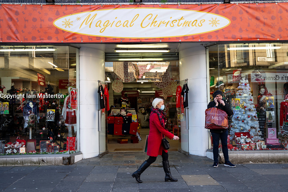 Glasgow, Scotland, UK. 19 November 2020. On the day before the highest level 4 lockdown is imposed on west and central Scotland, shops in Glasgow city centre and streets are busy with members of the public. Pictured; Woman walks past speciality Christmas store.  Iain Masterton/Alamy Live News