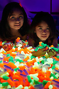 Two young girls lying down in front of a pile of glowing packing peanuts.Black light