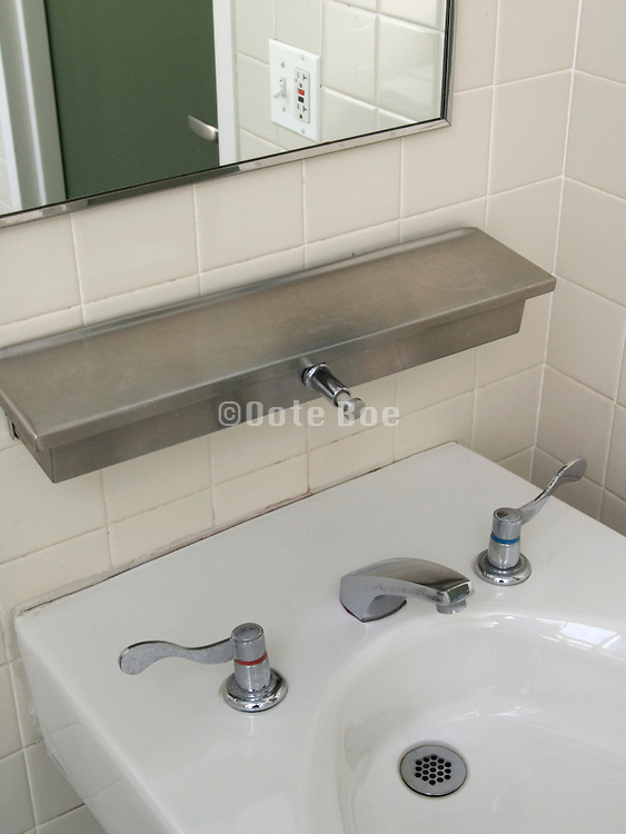 clean sink in bathroom with soap dispenser and mirror